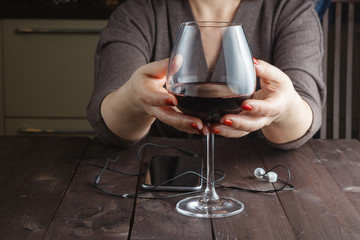 woman is holding in his hand a glass of alcoholic beverage