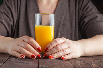 woman hand holding glass of orange juice