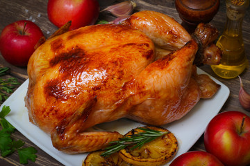 whole chicken noticed roasted with lemon and apples on a plate on a wooden background
