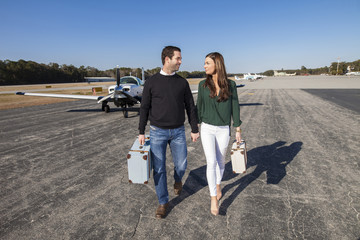 Trendy young couple with plane