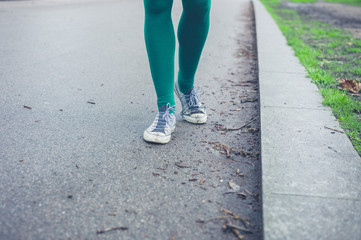 Legs of young woman walking outside