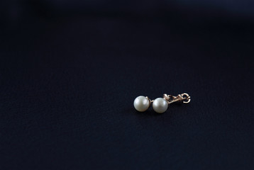 white pearls earrings on a dark blue background