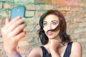 young pretty girl making selfie of her mustache hair
