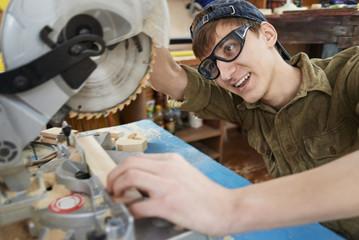 cutting wood pieces circular saw, a carpenter smiling
