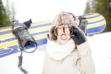 Snowboarding.Young beautiful woman with ski mask holding her snowboard at ski slope Young woman in ski resort holding snowboard on her shoulders and smiling.Concept of winter holiday
