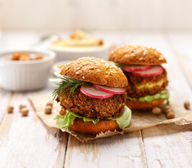 Falafel burger with addition of fresh  radish, onion, dill and Iceberg lettuce on a wooden rustic table. Healthy and delicious  vegetarian dish