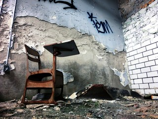 Desk inside abandoned school building with crumbling wall - landscape color photo