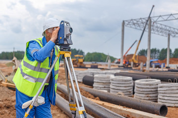 Man surveyor in the construction helmet makes measurements using surveying equipment