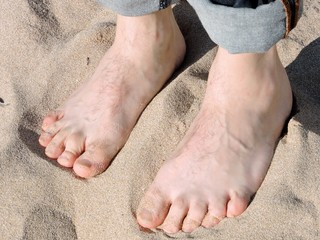Male bare feet on sand