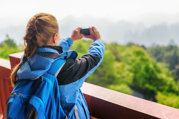 Young female tourist with smartphone taking photo of mountains