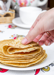 Takes hand and turns a pancake with red caviar