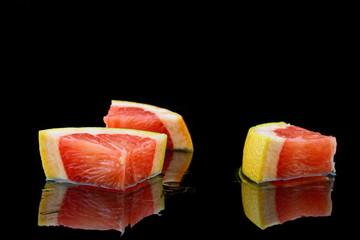 drei stückchen grapefruit auf schwarzen hintergrund