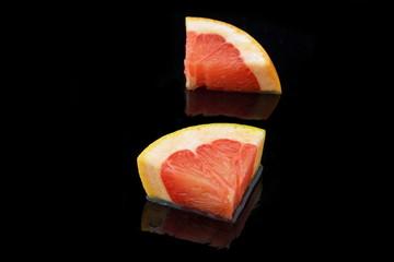 zwei stückchen grapefruit auf schwarzen hintergrund