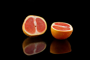 eine geteilte grapefruit auf schwarzen hintergrund