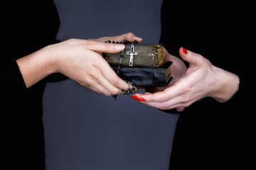 Woman gives two Bibles and rosary to another woman