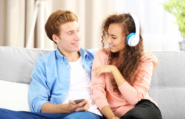 Teenager couple listening to music with mobile phone on a sofa