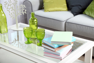 Low table with books and green glassware in living room