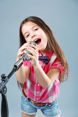 Beautiful artistic little girl with microphone on grey background