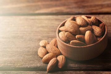 Almonds in the wooden bowl on the table, close-up