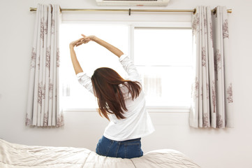 A asian Woman stretching in bed after wake up, back view