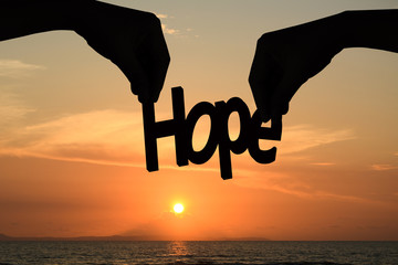 Silhouette hands holding the word hope. Background Sunset.