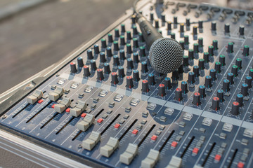 A closeup image of microphone on audio mixer's