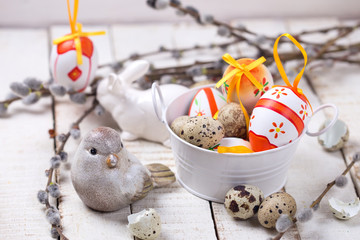 Colorful easter eggs in bucket,  decorative bird and willow  bra