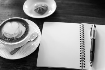 Coffee cup and notebook on table background.