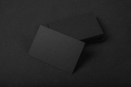 Stack Of blank black business cards on textile background