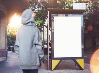 Photo of girl looking at empty lightbox on the bus stop. Horizontal