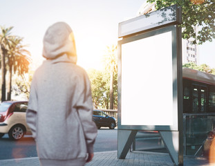 Photo of girl looking at blank lightbox on the bus stop. Horizontal