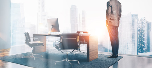 Photo of businessman stands in contemporary office. Wide