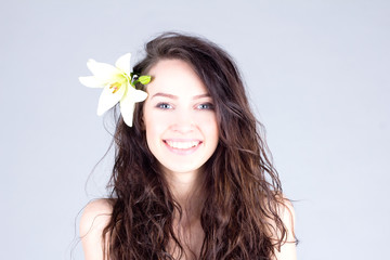 Happy woman with flower in curly hair with smile with teeth. SPA treatment.