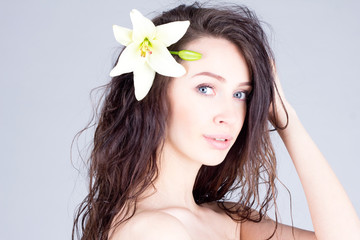Beautiful woman with flower in curly hair. SPA treatment.