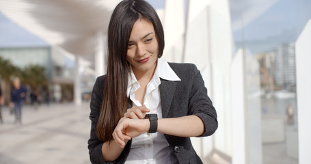 Young woman checking her wristwatch for the time as she walks down an urban promenade in the sunshine  close up upper body