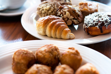 Breakfast consisting of croissant, bun, sweet, donut and banana balls on white plates