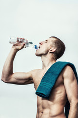 Muscular young man after a workout  drinking  bottle of water
