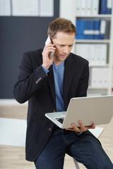 geschäftsmann mit laptop und mobiltelefon