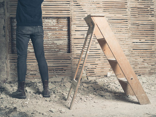 Person standing by wattle and daub walll with ladder