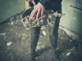 Hand with dustpan full of rubble