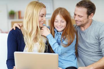 eltern und tochter schauen gemeinsam auf den laptop