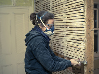 Young woman repairing wattle and daub wall