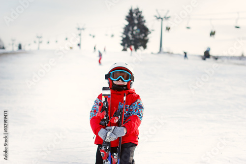 8763792513c0 Little cute boy with skis and a ski outfit.