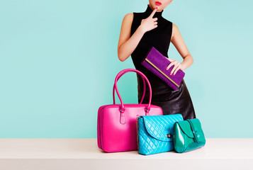 Wall Mural - Woman choosing the bag from many colorful bags.Isolated on light blue background. Shopping addiction.