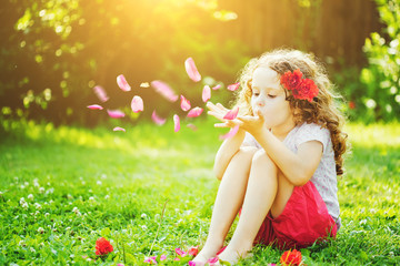 Little girl blowing flower petals from her hands in the sunlight