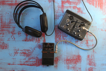 Guitar pedal, headset, and audio card on grunge background - music concept