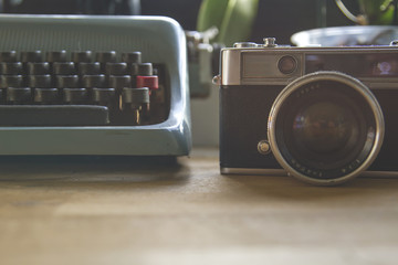 old photocamera and typewriter on a desk