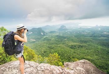Travel concept. Young woman tourist - photographer taking photo at mountain peak