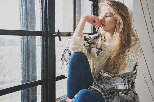 beautiful blonde woman thinking at home