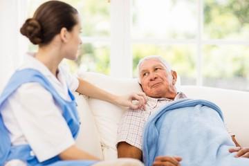 Nurse taking care of sick elderly patient